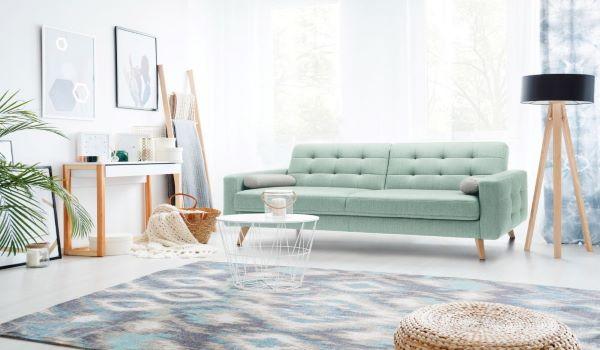 Złożona sofa w stylu skandynawskim Nappa marki Sweet Sit z drewnianymi nózkami, pikowanym oparciem i miętową tapicerką stoi pod oknem w pokoju nastolatki.