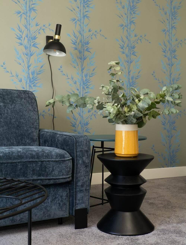 Bok sofy Jana marki Gala Collezione, przy którym stoi czarny stolik kawowy z wazonem. Na ścianie kinkiet Markslojd