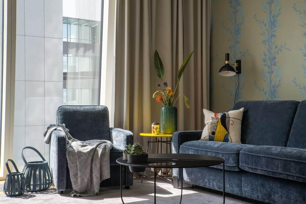 Fotel i sofa Jana marki Gala Collezione na tle dużego okna oraz ściany z tapetą z motywem bambusa