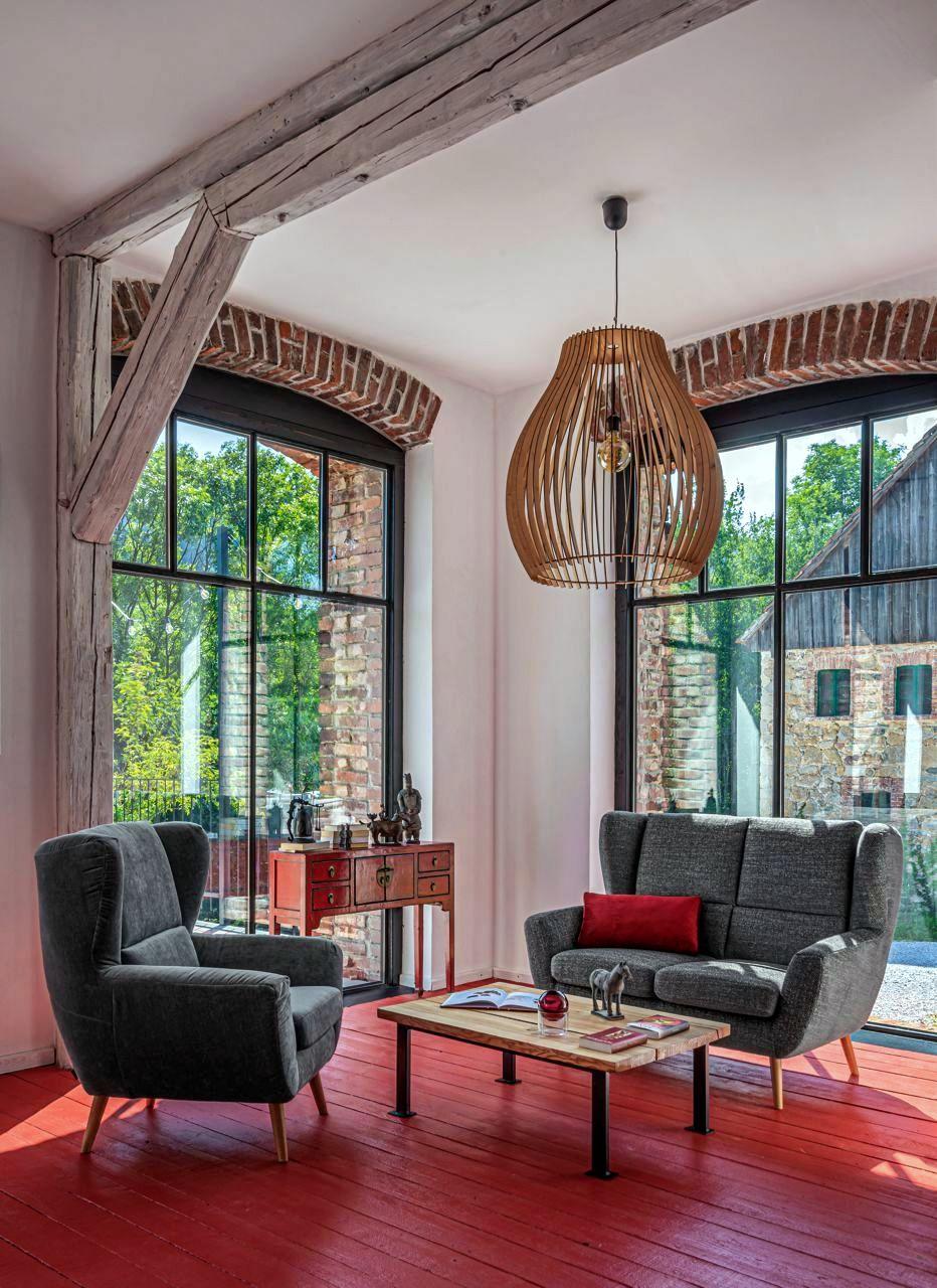 Sofa i fotel Forli w wiejskiej posiadłości z dużymi oknami