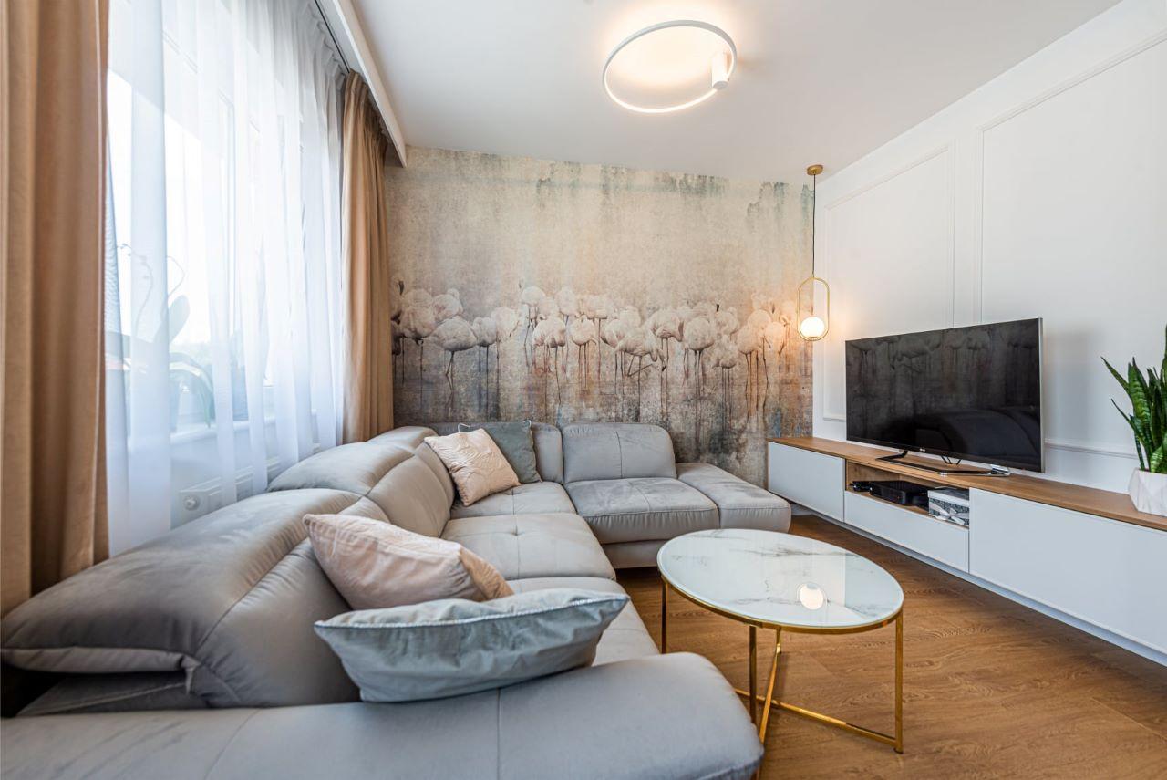 Narożnik Fava z kolekcji Gala Collezione w jasnej szarej tapicerce w nowoczesnym salonie na tle tapety w delikatne, pastelowe wzory.