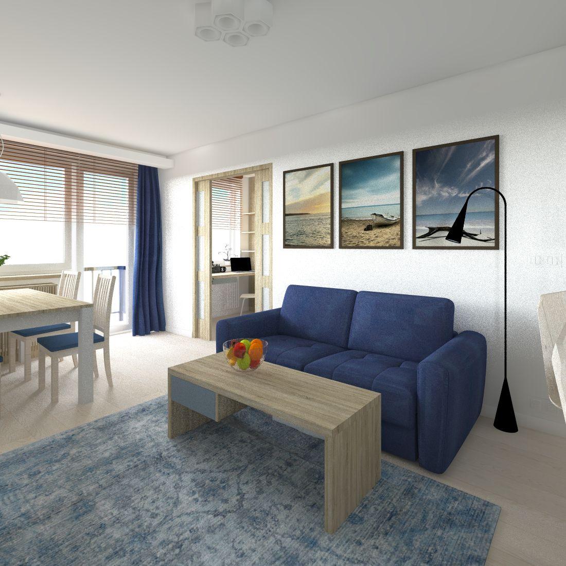 Granatowa sofa Olbia marki Gala Collezione, w tle wiszą kolorowe obrazki, stoi niski stolik kawowy oraz leży bladoniebieski dywan