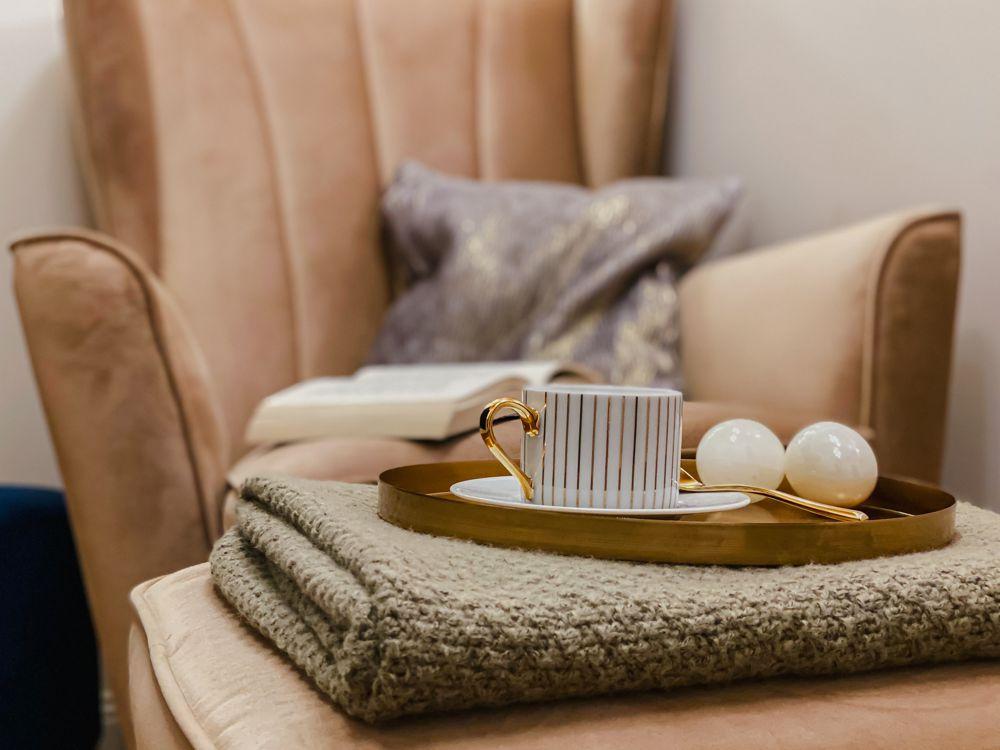 Fotel Fido marki Gala Collezione z niewielkim podnóżkiem, na którym stoi taca z filiżanką