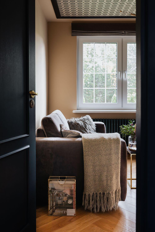 Pokój z sofa Sora marki Gala Collezione, widziany przez półotwarte granatowe drzwi