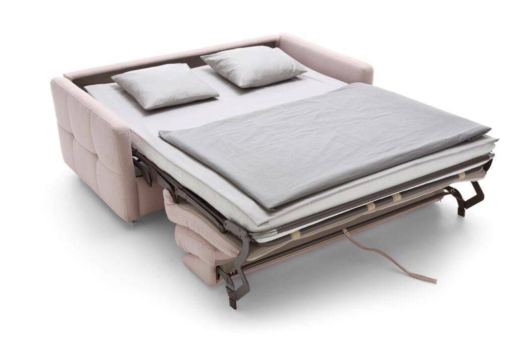 Sofa Ema marki Sweet Sit z rozłożoną funkcja spania typu stelaż włoski i pościelą.