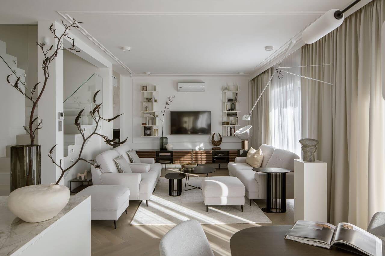 elegancki salon zaaranżowany w stylu modern classic z sofą, fotelami i pufami z kolekcji Monday Gala Collezione w jasnej tapicerce.